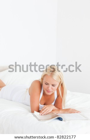 Portrait of a woman reading a magazine in her bedroom - stock photo