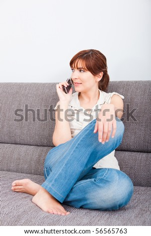 Portrait of a woman sitting on sofa, talking on phone - stock photo