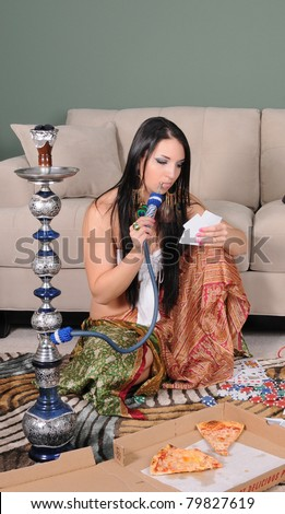 Portrait of a woman smoking hookah relaxing playing cards and eating pizza - stock photo