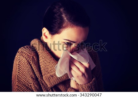 Portrait of a woman sneezing to tissue - stock photo
