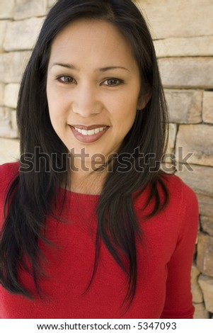 portrait of a woman standing in front of a rock wall - stock photo