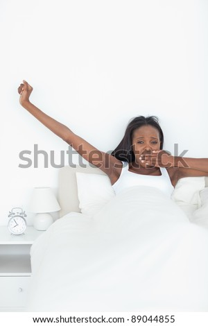 Portrait of a woman stretching her arms while yawning in her bedroom - stock photo