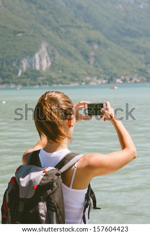 Portrait of a woman taking photos with mobile phone./ Back view of young woman taking photos with mobile phone.  - stock photo