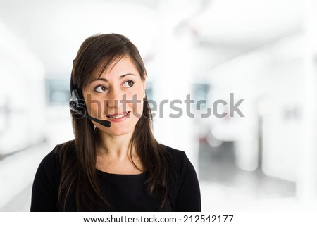 Portrait of a woman using an headset - stock photo
