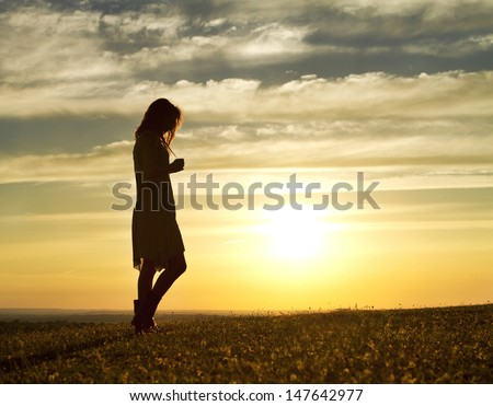 Portrait of a Woman walking thoughtfully at sunset - stock photo