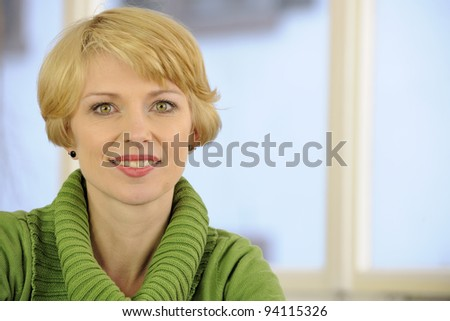 portrait of a woman wearing a green sweater with copyspace - stock photo