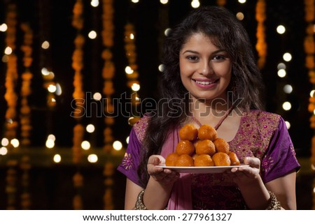 Portrait of a woman with a plate of sweets - stock photo