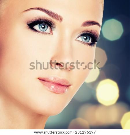 Portrait of  a  woman with beautiful blue eyes and long black eyelashes  - studio shot - stock photo