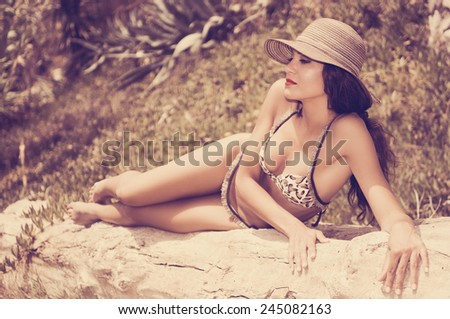 Portrait of a woman with beautiful body wearing bikini and sun hat - stock photo