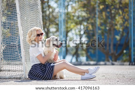 Portrait of a woman with beautiful dog playing outdoors. Beautiful woman playing with golden retriever. Outdoor portrait. series.  - stock photo