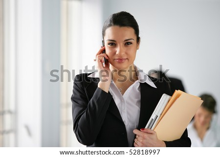 Portrait of a woman with cell phone and documents - stock photo