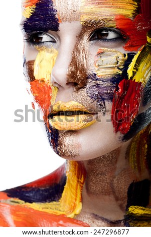 Portrait of a woman with colorful paint brushstroken on face - stock photo