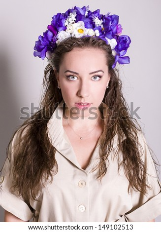 portrait of a woman with flowers studio gray background - stock photo