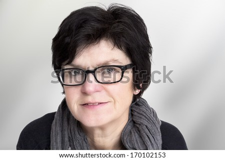 Portrait of a woman with glasses in middle age - stock photo