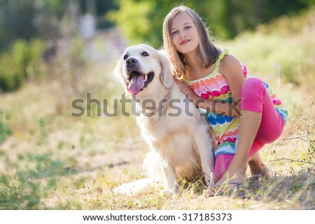 Portrait of a woman with her beautiful dog outdoors. Cute little girl hugging golden retriever. Young girl with golden retriever walking away into sun  - stock photo