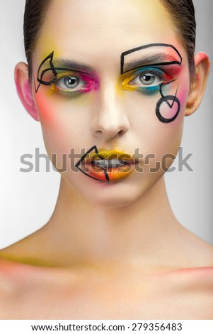Portrait of a woman with make-up and drawings on his face close up - stock photo