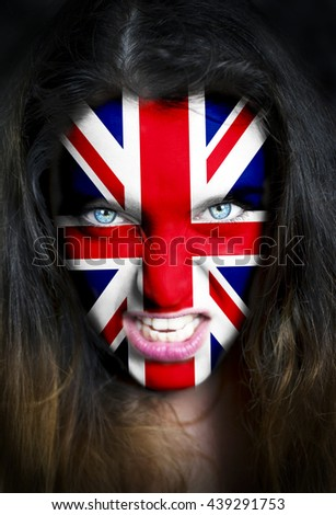 Portrait of a woman with the flag of the  United Kingdom painted on her face. - stock photo