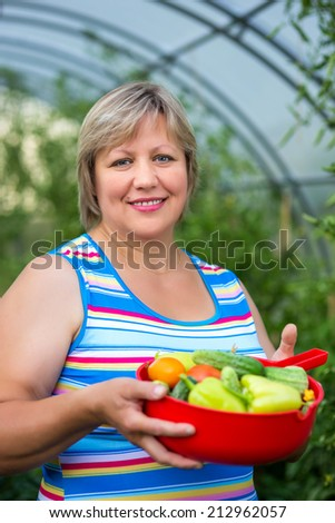 Portrait of a woman with vegetables in a bowl near greenhouses - stock photo