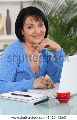 Portrait of a woman working on her laptop - stock photo