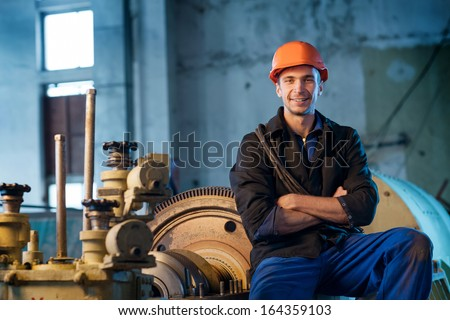 Portrait of a worker in the helmet near the steam turbine - stock photo