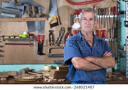 Portrait of a worker in work clothes in front of workbench tools / Portrait of man at work in workshop in garage at home  - stock photo