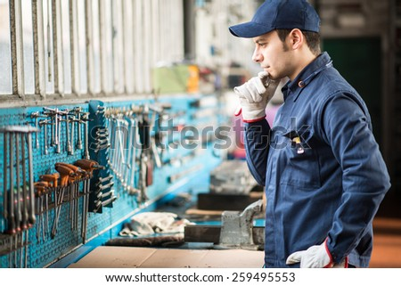 Portrait of a worker searching for the right wrench - stock photo