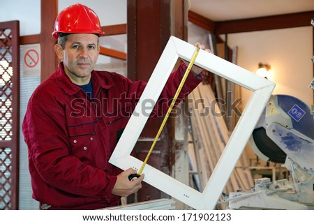 Portrait Of A Worker Using A Tape Measure. Worker measuring a pvc window frame in a workshop. - stock photo