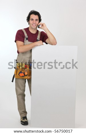 Portrait of a worker with mobile phone leaning on a white panel for message - stock photo