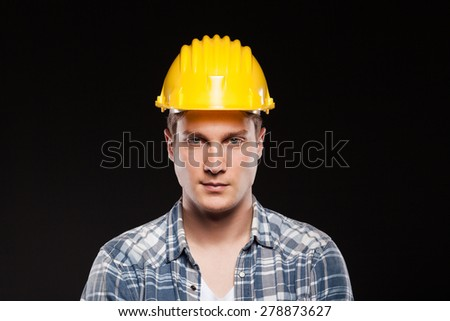 portrait of a worker with yellow helmet on head, isolated on black background - stock photo