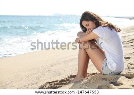 Portrait of a worried girl sitting on the beach with the sea in the background      - stock photo
