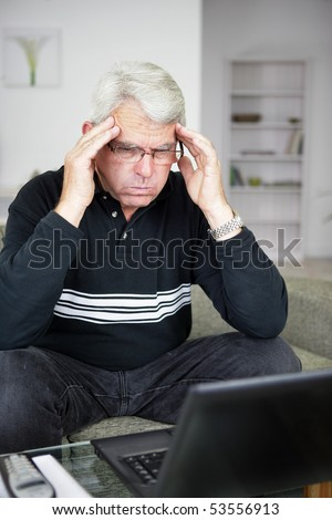Portrait of a worried man trying to concentrate in front of a laptop computer - stock photo