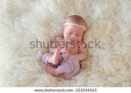 Portrait of a yawning ten day old newborn baby girl. She is curled up and sleeping on her back on a cream colored flokati rug. - stock photo