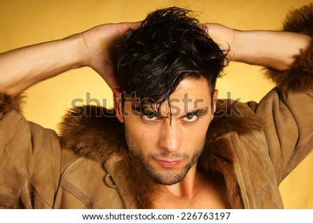 Portrait of a 30 year old caucasian man wearing a brown leather jacket with fur over a yellow background. - stock photo