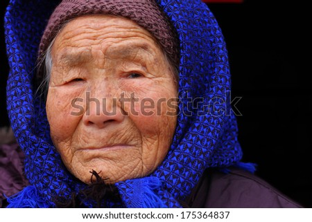 Portrait of a 95 years old woman, born in 1919, with depression,  the last generation that bind the feet of woman - stock photo