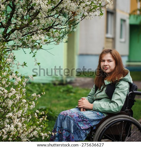 Portrait of a yong beautiful woman smiling in a wheelchair in the park. Green background. Spring day. - stock photo