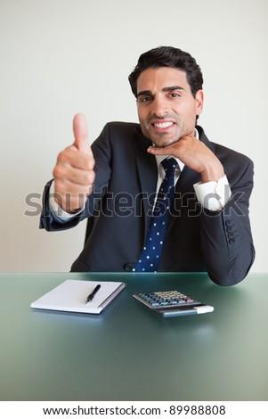 Portrait of a young accountant with the thumb up in his office - stock photo