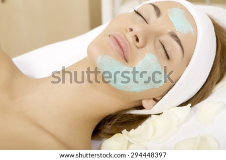 Portrait of a young adult beautiful attractive sensuality pretty brunette woman getting beauty skin mask treatment on her face with brush - stock photo