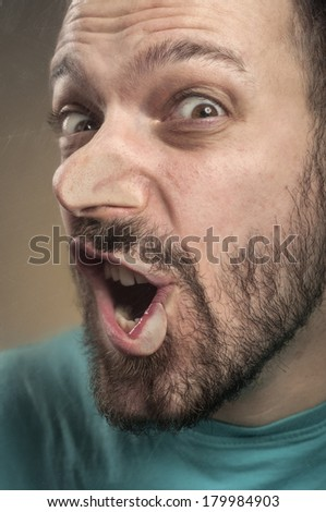 Portrait of a young adult man with beard smashing his face against the scratched glass - stock photo