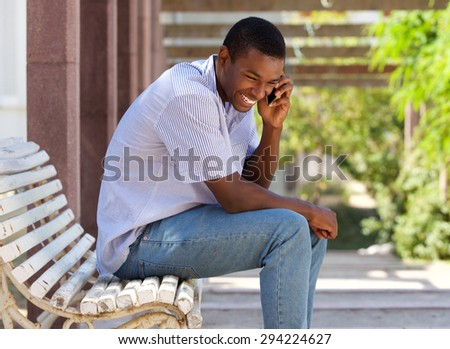 Portrait of a young african american man laughing with mobile phone outside - stock photo
