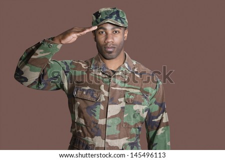 Portrait of a young African American US Marine Corps soldier saluting over brown background - stock photo