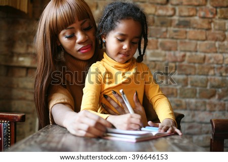 Portrait of a young African American woman and her daughter writing. - stock photo
