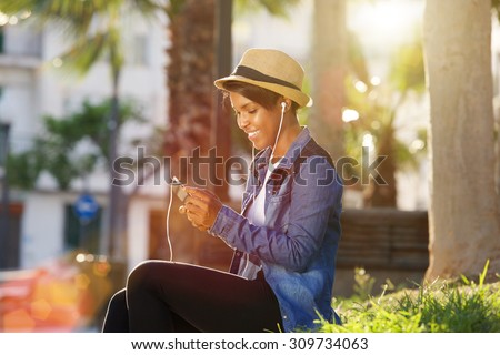 Portrait of a young african american woman listening to music on cell phone - stock photo