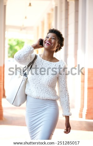 Portrait of a young african american woman walking and talking with cellphone  - stock photo