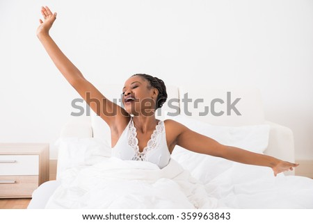 Portrait Of A Young African Woman Stretching Her Arms On Bed - stock photo