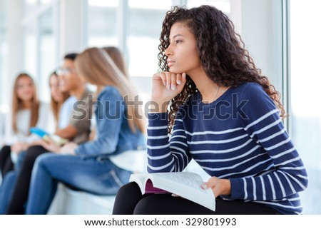 Portrait of a young afro american woman holding book and thinking about something in university hall - stock photo