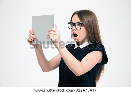Portrait of a young amazed woman looking on tablet computer screen isolated on a white background - stock photo