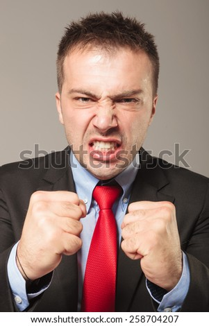 Portrait of a young angry business man showing you his fists. - stock photo
