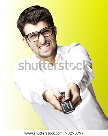 portrait of a young angry man holding a remote control over a yellow background - stock photo