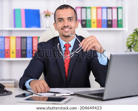 Portrait of a young Asian businessman, using laptop, sitting in office - stock photo