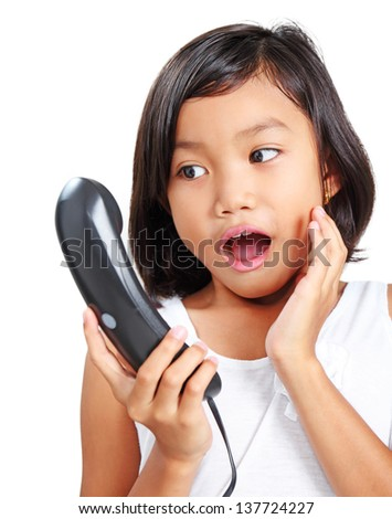Portrait of a young asian girl receiving a surprised telephone call. - stock photo